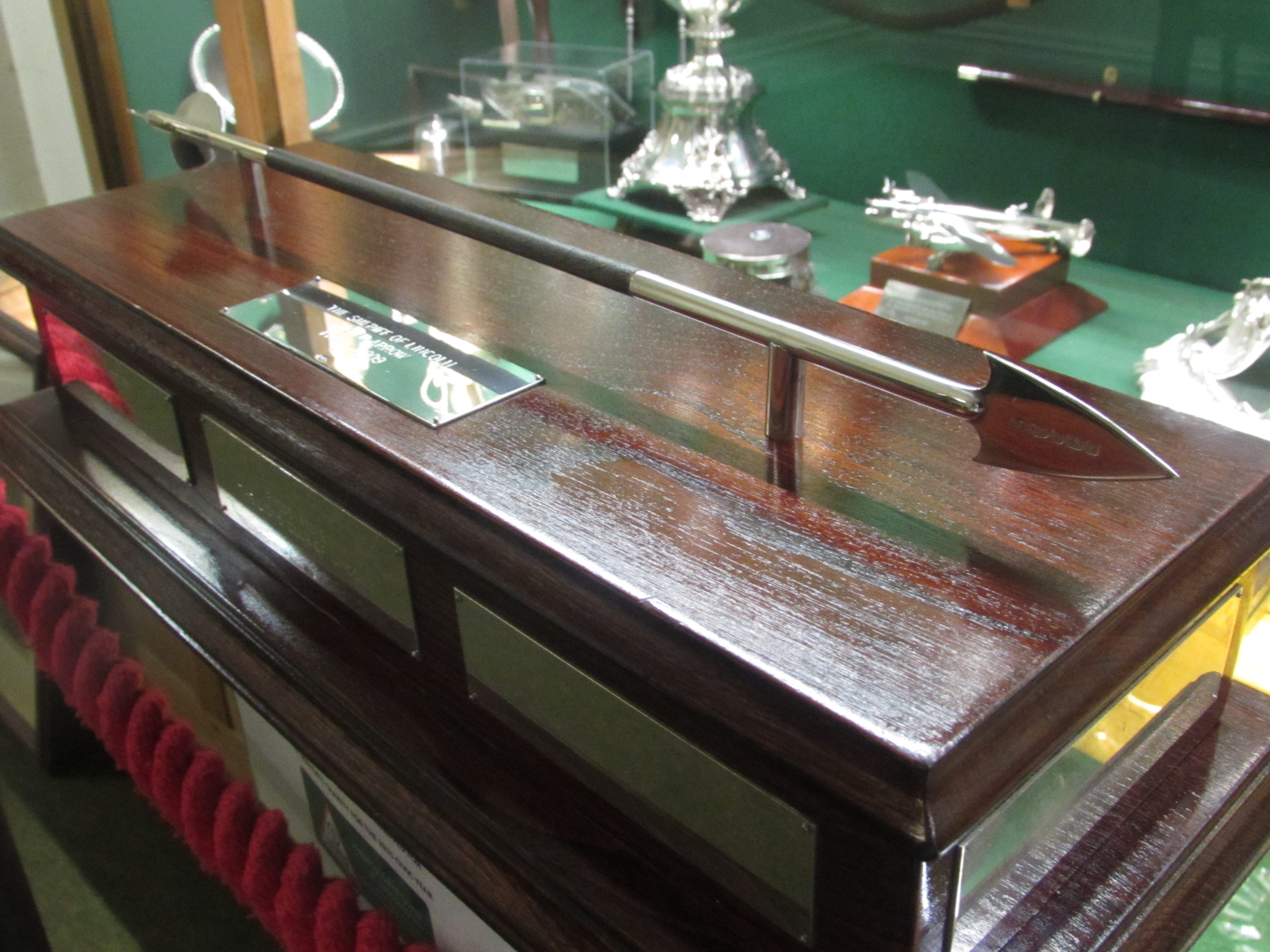 Picture of a silver arrow in a display cabinet.