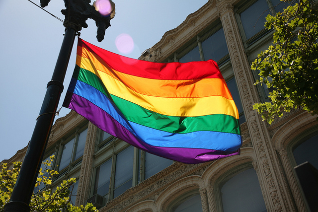 An LGBT+ rainbow pride flag is tied to a flagpost, waving in the wind. A grey building with many windows, some leafy trees and a blue sky are in the background.